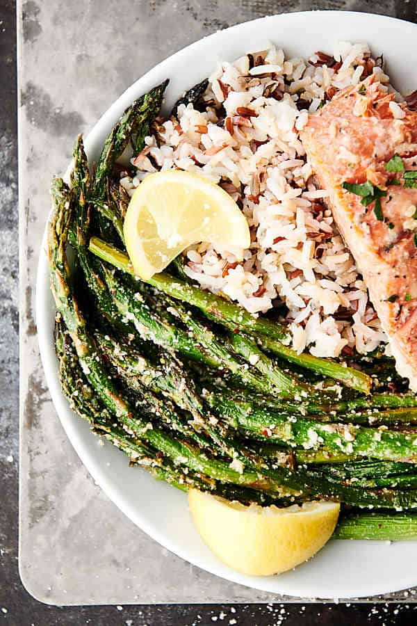 plate of lemon parmesan roasted asparagus with rice and salmon above