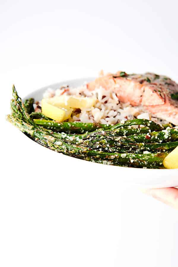 lemon parmesan roasted asparagus on plate held