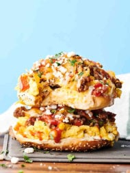 Sausage, Egg, and Cheese Breakfast Pizza Bagels Recipe. Everything bagels smothered in cream cheese and loaded with breakfast sausage, onion, bell peppers, fluffy scrambled eggs, mozzarella, and cheddar cheese. showmetheyummy.com #breakfast #pizza #bagels #sausage #eggs #cheese