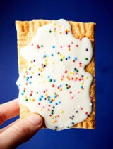 These air fryer strawberry pop tarts are made with pre-made refrigerated pie crusts, strawberry jam, and drizzled in a simple glaze: powdered sugar, heavy cream, melted butter, and vanilla extract. Don't forget the sprinkles! showmetheyummy.com #airfryer #strawberry #poptarts #homemade