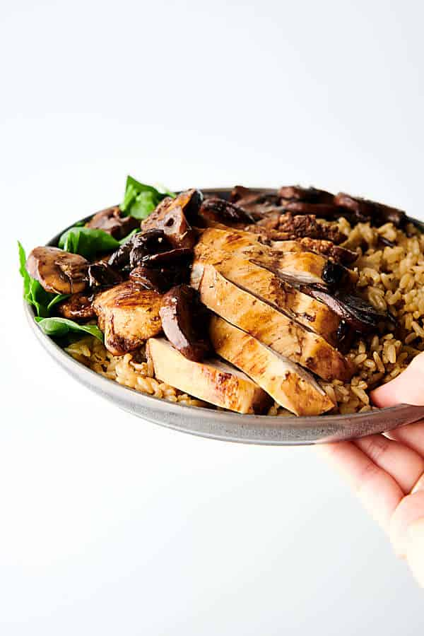 one pan balsamic chicken holding in hand