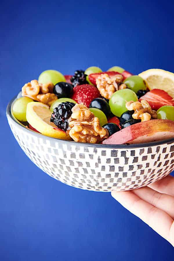 fruit salad with honey walnuts blue background