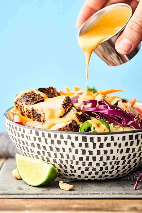 grilled pork spring roll bowls drizzling with peanut sauce