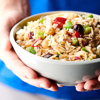 holding Greek orzo salad