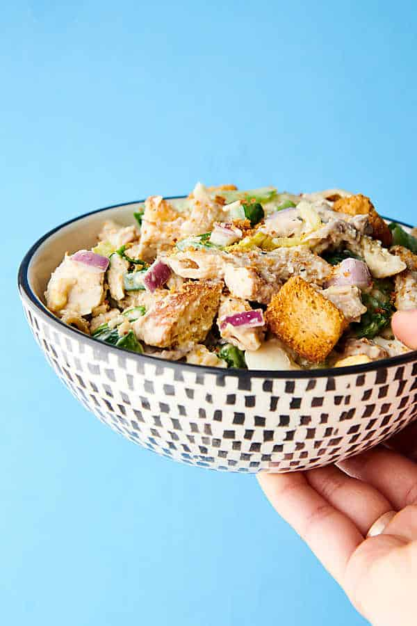 healthy chicken caesar pasta salad holding in hands blue background