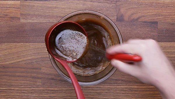 ladleful of sugar mixture being whisked into egg mixture