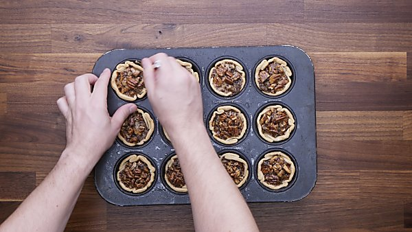 finished mini pecan pies, one being taken out of muffin tin