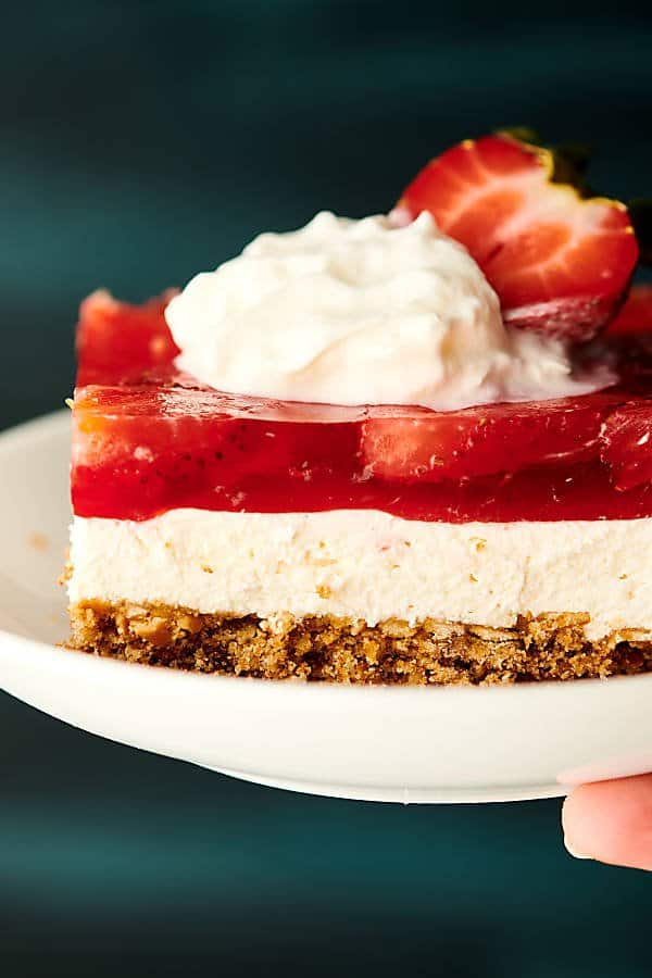 strawberry pretzel salad on plate with whipped cream