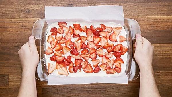 cream cheese mixture and strawberries layered in baking dish