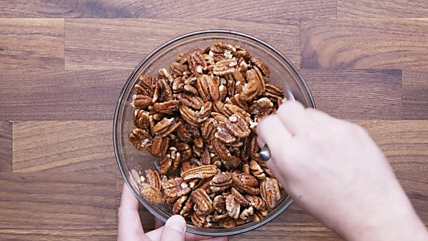 Pecans being mixed into egg white mixture