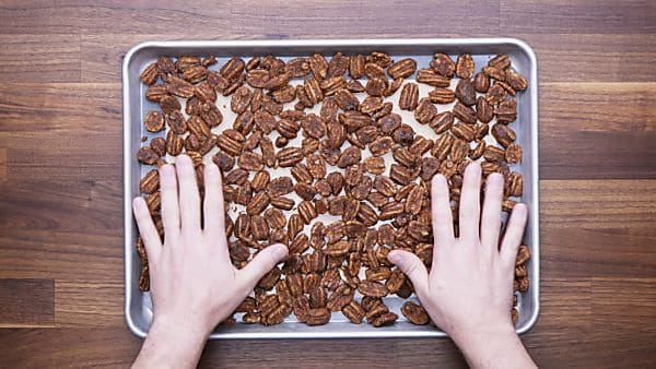 Pecans being spread on baking sheet