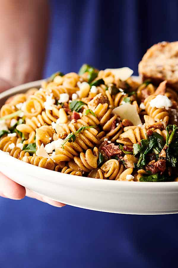 holding a plate of healthy sun dried tomato and arugula pasta