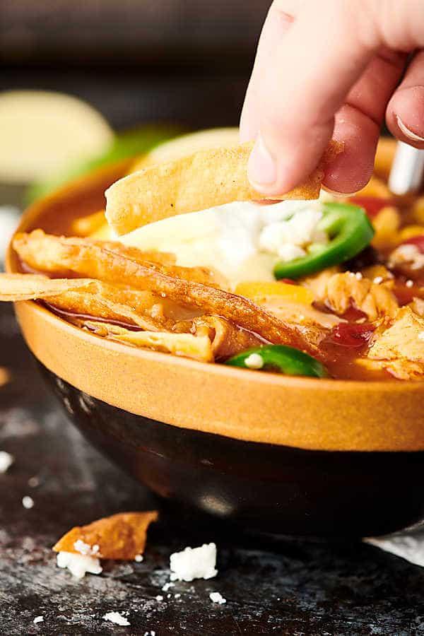 Instant Pot Chicken Tortilla Soup holding crispy tortilla strips