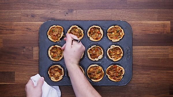 Mini chicken pot pies baked; one being taken out