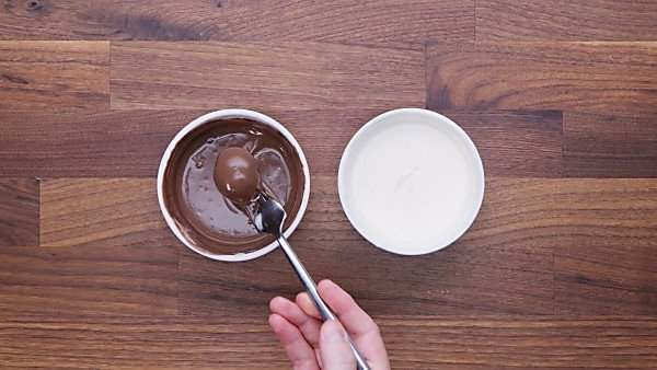 Oreo ball being dipped into melted chocolate