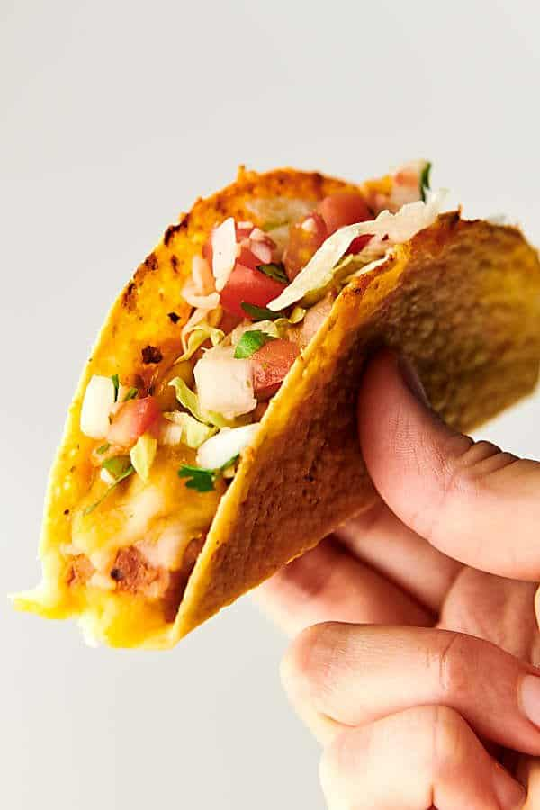 holding Supreme Pizza Tacos