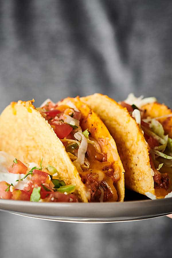 holding Supreme Pizza Tacos on a plate