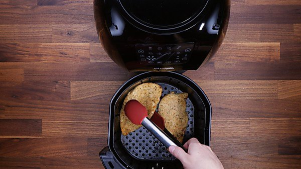 Cooked air fryer chicken piccata in being taken out of air fryer with tongs