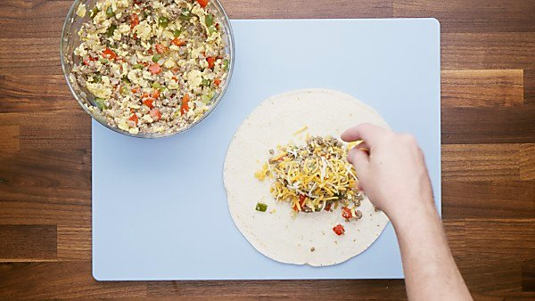 Burrito fillings being put on tortilla