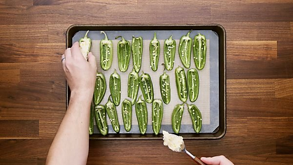 Jalapeno halves being filled with cream cheese mixture and placed on baking sheet