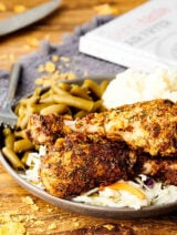 Air fryer fried chicken on a plate with green beans and potatoes
