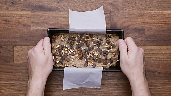 Unbaked banana bread topped with pecans and chocolate chips