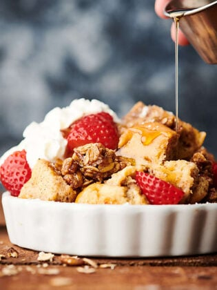 French toast casserole with strawberries and whipped cream and maple syrup drizzled