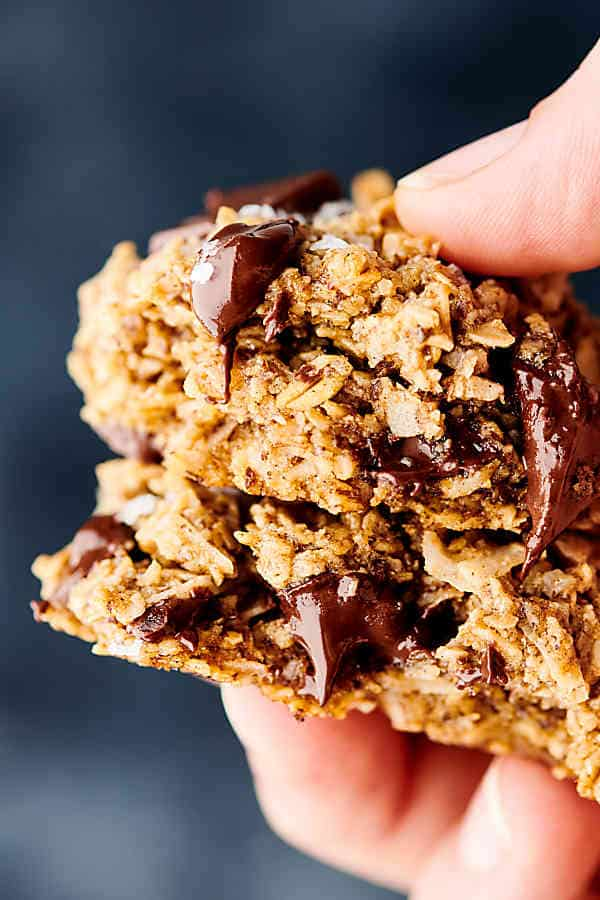 Close up of two oatmeal chocolate chip cookies being held