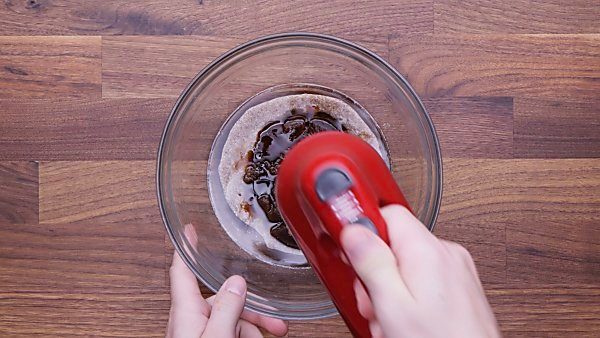 Wet ingredients being mixed with hand beater