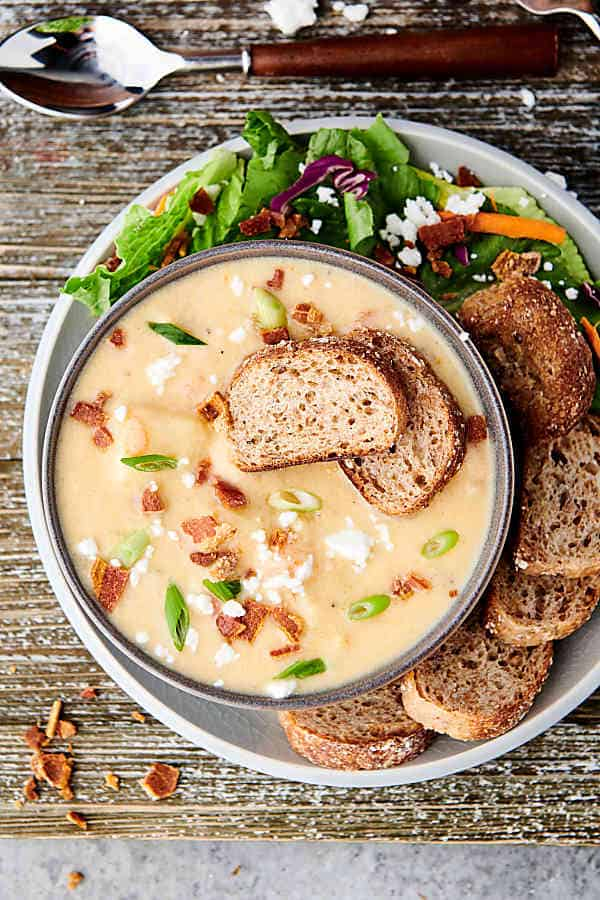 Overhead shot of bowl of instant pot potato soup with garnishes on a plate with bread and salad