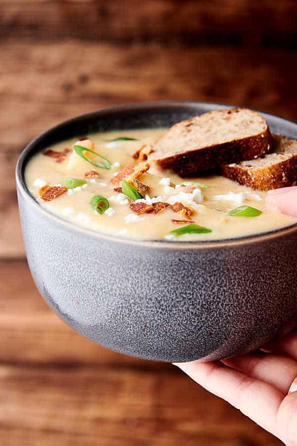 Bowl of instant pot potato soup with garnishes and two slices of bread being held