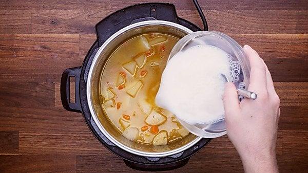 Cornstarch/milk mixture being poured into potato soup