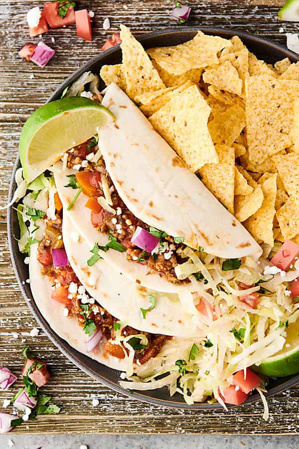 Two instant pot turkey tacos on a plate with tortilla chips and lime taken from above