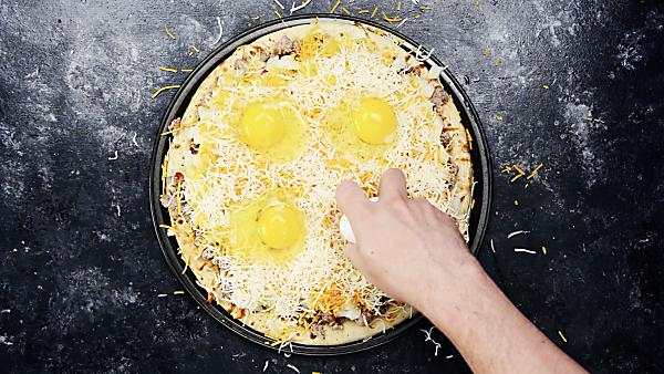 Eggs being cracked on top of pizza