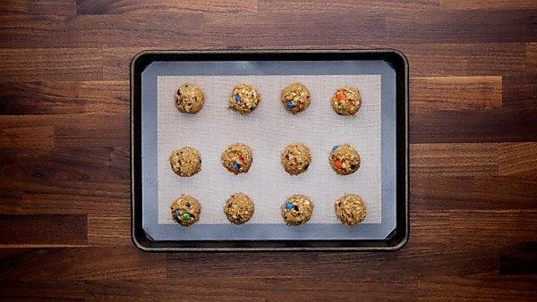 Balls of monster cookie dough on baking sheet