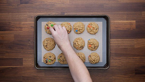 Baked monster cookies being topped with additional M&Ms