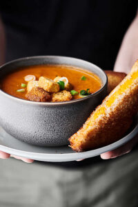 Bowl of roasted tomato soup on a plate with grilled cheese sandwich