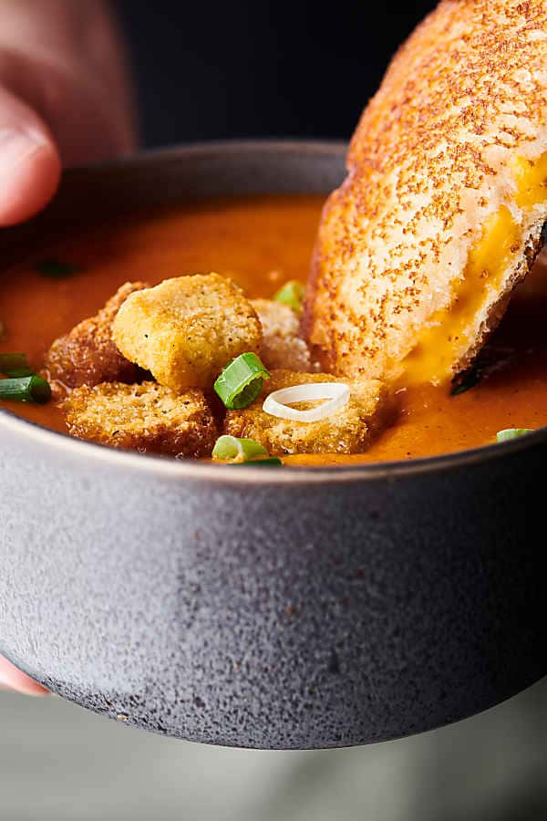Grilled cheese sandwich being dipped into bowl of roasted tomato soup