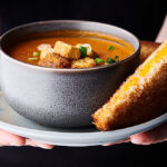 Bowl of roasted tomato soup on a plate with grilled cheese held