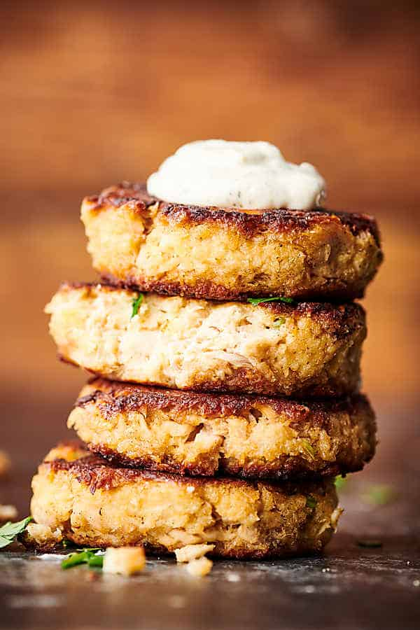 Four salmon patties stacked with a dollop of tartar sauce on top