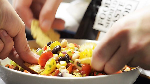 Chips being dipped into bowl of texas caviar