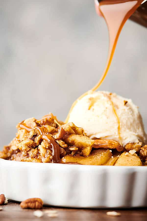 Dish of apple crisp with vanilla ice cream and caramel sauce being drizzled on top side view