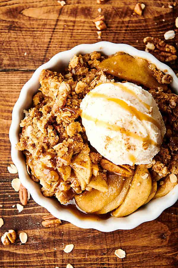 Dish of apple crisp recipe with ice cream and caramel drizzle above
