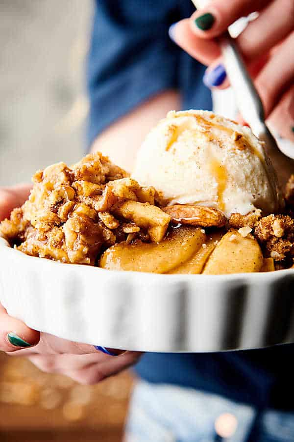 Dish of apple crisp with ice cream and caramel drizzle held with fork