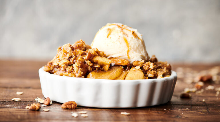 Dish of apple crisp recipe with ice cream scoop and caramel drizzle side view