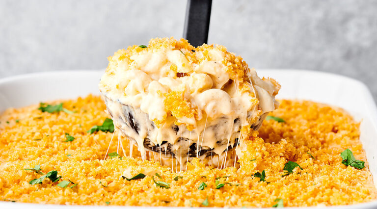 Ladle of baked mac and cheese being lifted out of baking dish