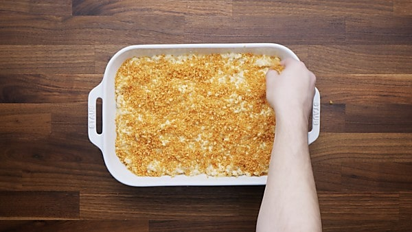 Topping being spread over baked mac and cheese