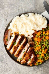 Plate of sliced pork chop, peas and carrots, and mashed potatoes above