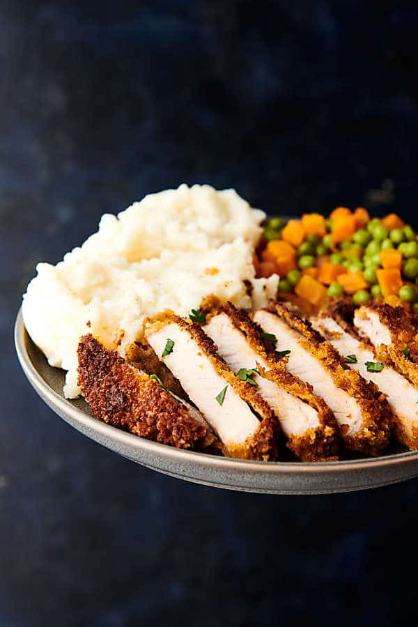 Plate of baked pork chop slices, carrot and peas, and mashed potatoes held side view