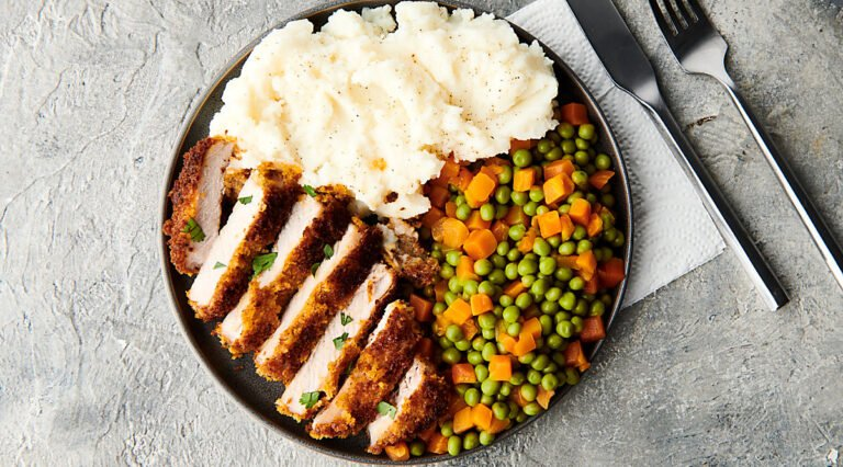 Plate of sliced pork chop, mixed peas and carrots, and mashed potatoes above